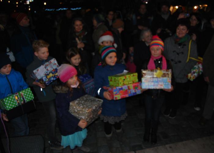 Beim Altstadtweihnachtsmarkt geben die Kinder der Klassen 4 der Grundschule Farrnbach ihre Päckchen ab