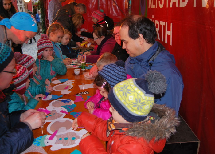 Die United Kiltrunners und Running Angel Susanne Singer basteln mit Kindern auf der Fürther Altstadtweihnacht